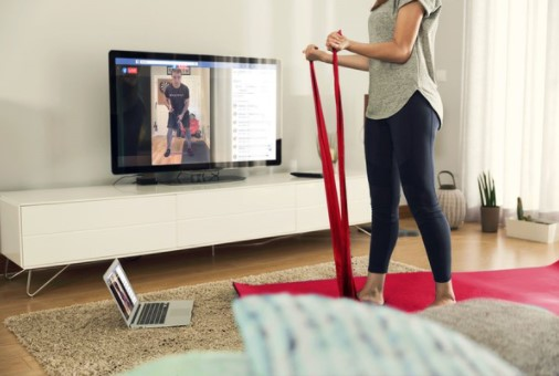 A woman exercises with resistance bands while watching a virtual personal trainer on a TV screen
