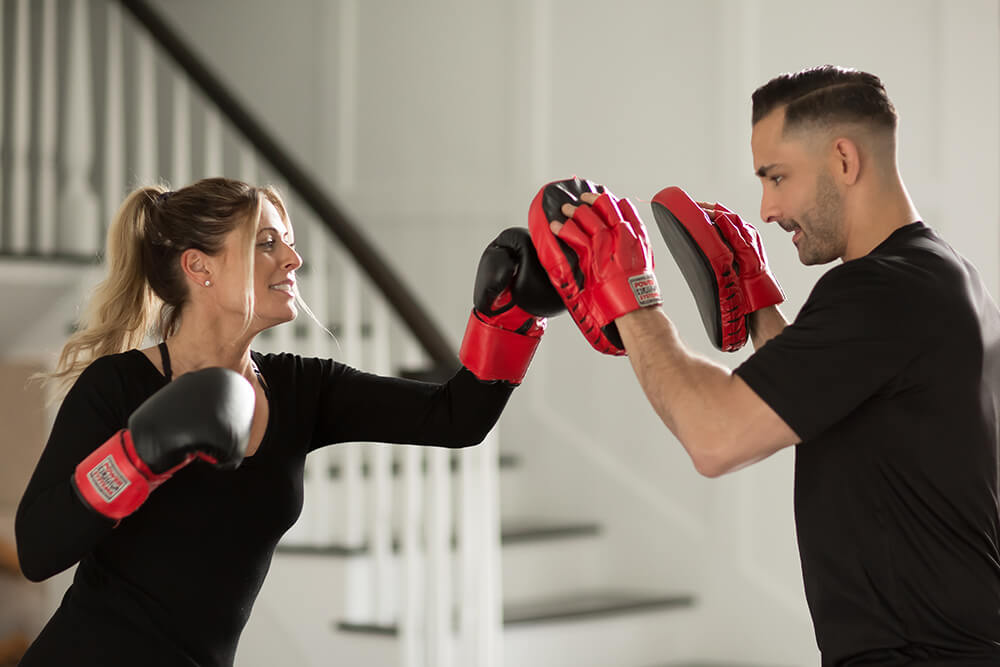A woman wearing boxing gloves punches practice pads held by a personal trainer