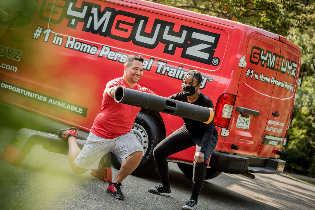 A man performs a workout with a personal trainer in Frisco